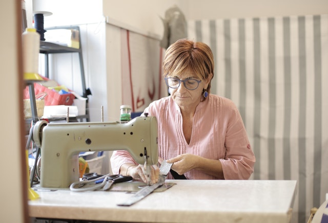 žena šije na šicím stroji